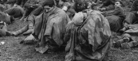 28th March 1945:  Tired and disconsolate German prisoners of war crouch under waterproof capes after their capture on the banks of the Rhine.  (Photo by Fred Ramage/Keystone/Getty Images)